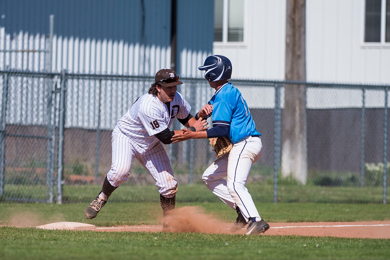 Jaxon Knight (18), of Davis, tries to stop the runner, Carson Lomax (11), of Layton, but his teammate, Stockton Hall, made an error and hit Lomax with the ball, allowing him to advance to third base, at Davis High School, in Kaysville, on May 5, 2017.