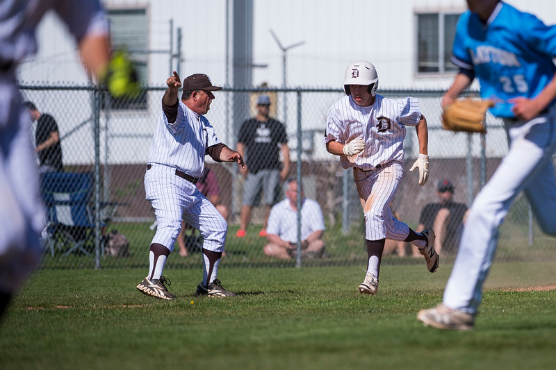 Zack Mansfield (21), of Davis High, is waved home after a base hit by his teammate, Stockton Hall, at Davis High School, in Kaysville, on May 5, 2017.