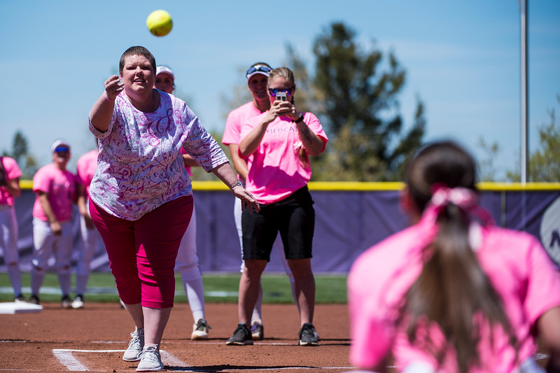 Karen Pestka, a breast cancer survivor, throws out the first pitch to her daughter, Courtney Pestka (9), of Weber State, to start out the game against the University Montana, at Weber State University, in Ogden, on Friday, May 5, 2017. The entire Weber State team wore pink uniforms in support of breast cancer survivors during Friday's game.