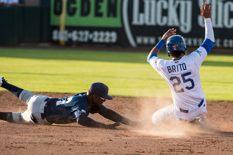 Ronny Brito (25), of Ogden, avoids the tag of Franly Mallen (17), of Helena, to steal second base at Lindquist Field, in Ogden, on Monday July 17, 2017.
