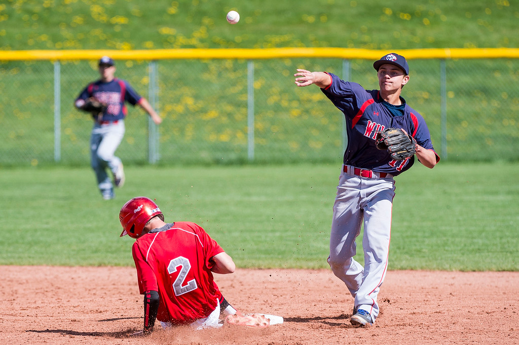 Woods Cross second baseman Zach McMillan (11), makes the out at second on Bountiful player David Stanger (2), of Bountiful High, but comes up just short of throwing out the batter Cooper Ohlson (3), of Bountiful, for the double play at Bountiful High School, in Bountiful, on Friday, April 21, 2017.