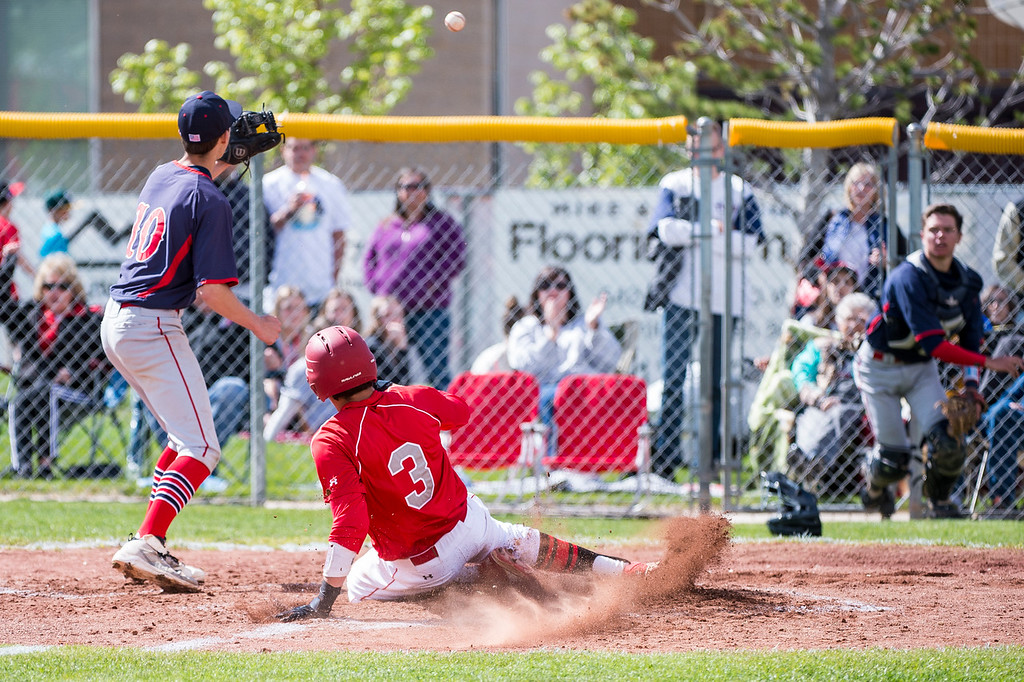 Cooper Olson (3), of Bountiful High, scores on a wild pitch by Woods Cross pitcher Austin Busdicker (10), at Bountiful High School, in Bountiful, on Friday, April 21, 2017.