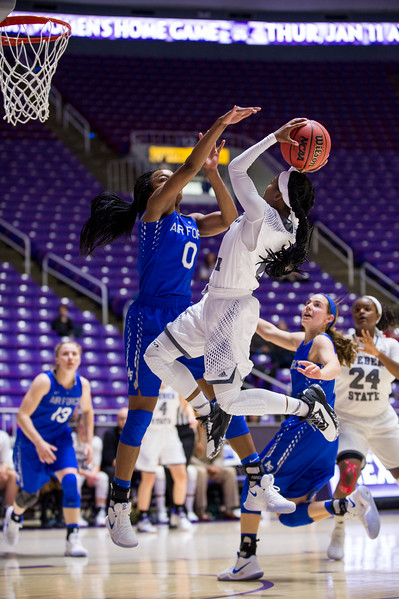 Weber State guard, Jaiamoni Welch-Coleman (0), drives and scores over the defense of Air Force player, Dee Bennett (0), at the Dee Events Center, in Ogden, on Saturday, December 9, 2017.
