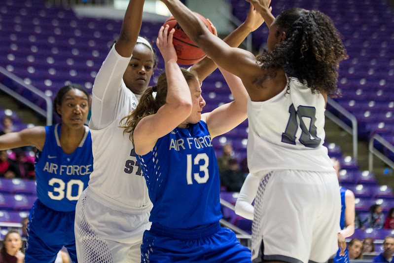 Weber State defenders, Dominique Williams (24) and Shine Johnson (10), force Emily Conroe (13), of Air Force to make a three second violation after she came up with an offensive rebound, at the Dee Events Center, in Ogden, on Saturday, December 9, 2017.