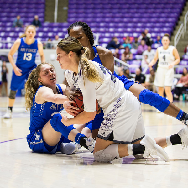 Weber guard, Emily Drake (20), fights to get the ball back after having it knocked loose by Air Force defender, Kaelin Immel (32, left), while Dee Bennett (0, right, behind) joins in on the battle for the ball, at the Dee Events Center, in Ogden, on Saturday, December 9, 2017.