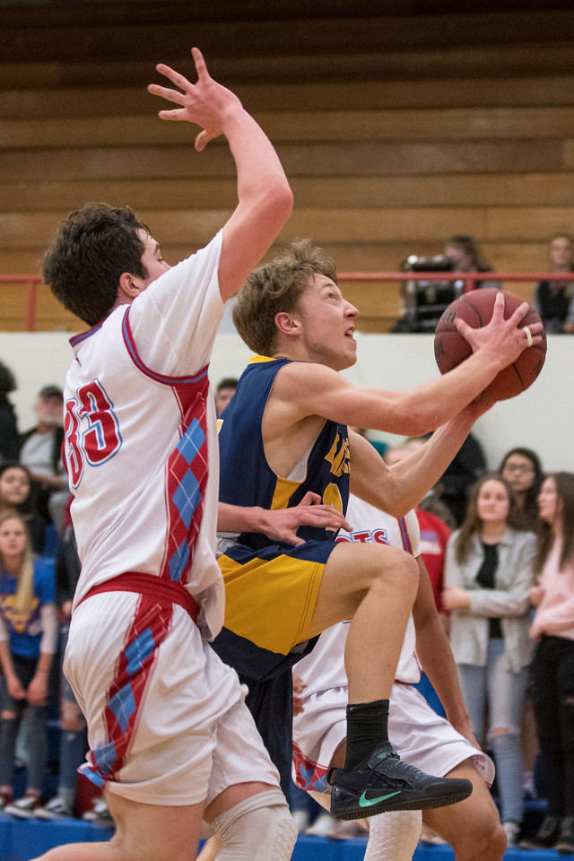 Caden Heaton (4), of Bonneville, tries to finish off a fast break opportunity, but is fouled by Titus Hughes (33), of Ben Lomond, at Ben Lomond High School, in Ogden, on Wednesday, January 17, 2018.