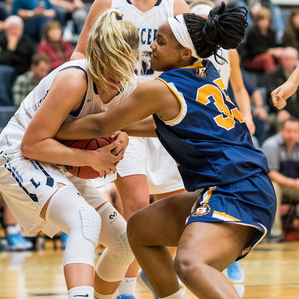 Gracey Criswell (21), of Layton High, battles for a loose ball against M. Johnson (35), of Bonneville High, at Layton High School, in Layton, on Tuesday, November 21, 2017.