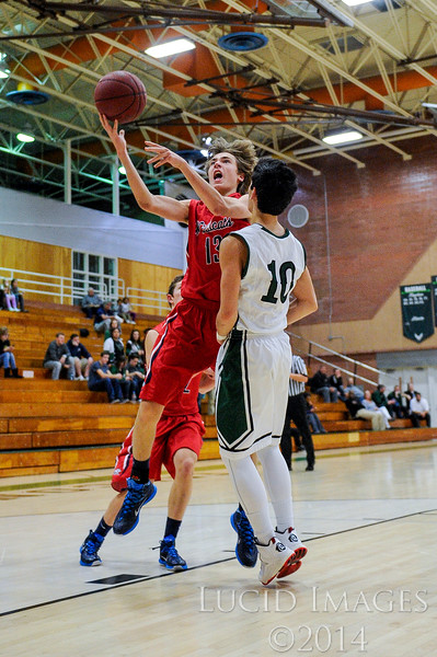 Zach Parrish (13), of Woods Cross High, goes up for a lay-up against defender Scotty Burkey (10), of Clearfield High, after a loose ball fast break at Clearfield High School in Clearfield on January 9, 2015. The Wildcats controlled the tempo of the game with their aggressive defense and the Falcons struggled to get points on the board for much of the first half.