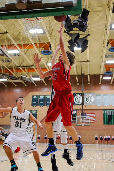 Zach Parrish (13), of Woods Cross High, goes up for a lay-up past defender Cameron Hamer (35), of Clearfield High, after a loose ball fast break at Clearfield High School in Clearfield on January 9, 2015. The Wildcats controlled the tempo of the game with their aggressive defense and the Falcons struggled to get points on the board for much of the first half.