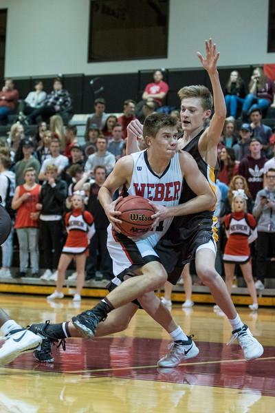 Austin Bartholomew (11), of Weber, drives to the basket, despite the tough defense of Davis player, Trevan Leonhard (2), at Weber High School, in Pleasant View, on Tuesday, January 23, 2018.