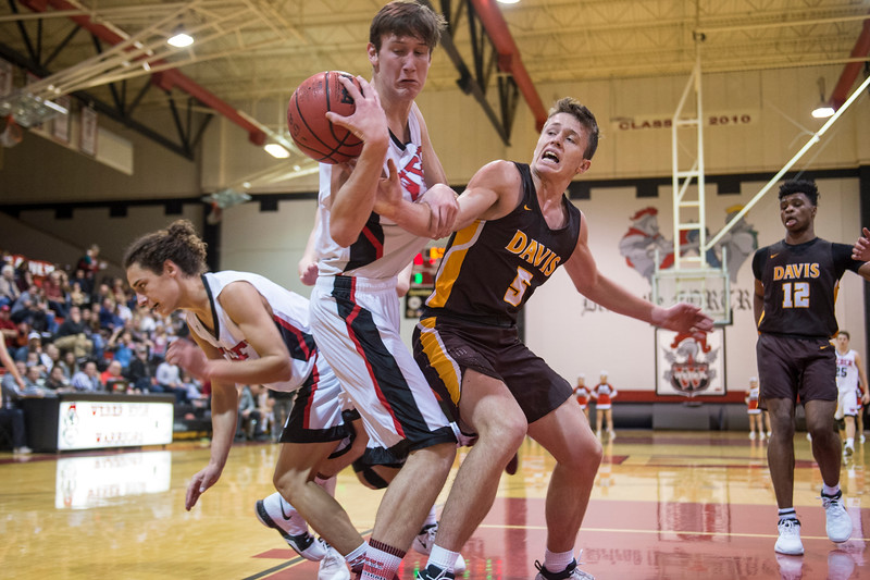 Braedon Iverson (5), of Weber, battles along the baseline for a loose ball rebound with Josh Sanders (5), of Davis, at Weber High School, in Pleasant View, on Tuesday, January 23, 2018.