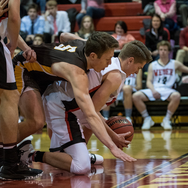 Josh Sanders (5), of Davis, puts pressure on Weber player, Brandon Capener (22), resulting in an offensive rebound for Davis and ultimately foul shots, at Weber High School, in Pleasant View, on Tuesday, January 23, 2018.