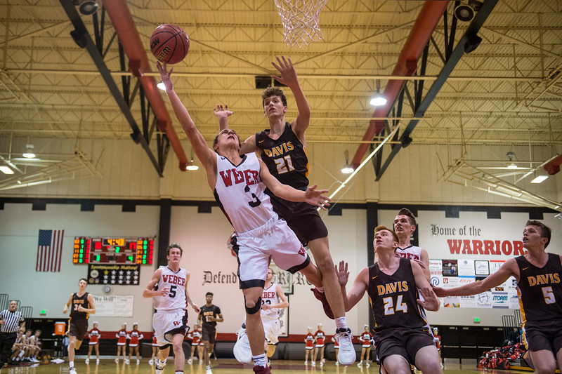 Hudson Schenck (3), of Weber, gets fouled trying to complete a fast break, getting sent to the free-throw line by Davis defender, Tyson Garff (21), at Weber High School, in Pleasant View, on Tuesday, January 23, 2018.