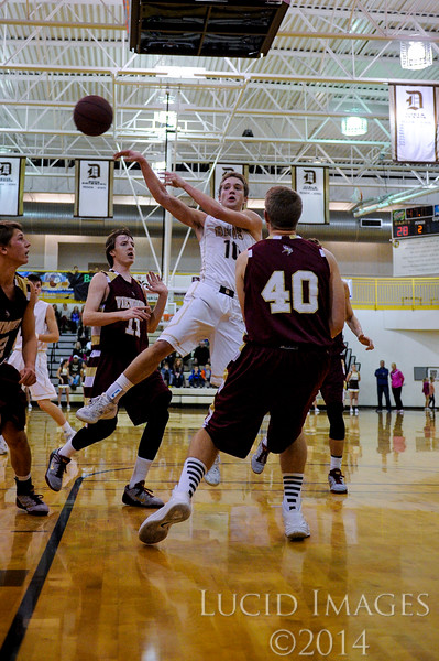 Hayden Grange (11), of Davis High, kicks a no-look pass out to teammate Landon Swartz (3) who then knocked down a three pointer to widen their double digit lead over Viewmont High even further at Davis High School in Kaysville on January 13, 2015.