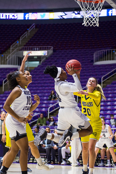 Jaiamoni Welch-Coleman (0), of Weber State, makes a difficult lay up after almost getting stopped by the defense of Northern Arizona player, Lauren Orndoff (20), at the Dee Events Center, in Ogden, on Saturday, February 3, 2018.