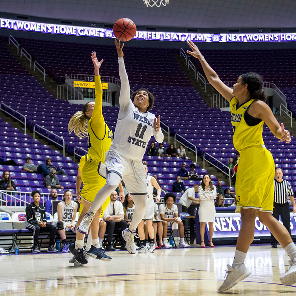 Weber State's leading scorer, Larryn Brooks (11), drives to the basket past the defense of Lauren Orndoff (20), for a lay up in the game's final minutes to help seal their win against Northern Arizona, at the Dee Events Center, in Ogden, on Saturday, February 3, 2018.