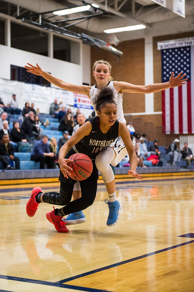 Corinne Case (3), of Layton, trips up Michaela Harris (10), as she tries to drive to the basket, at Layton High School in Layton, on Wednesday, January 3, 2018.