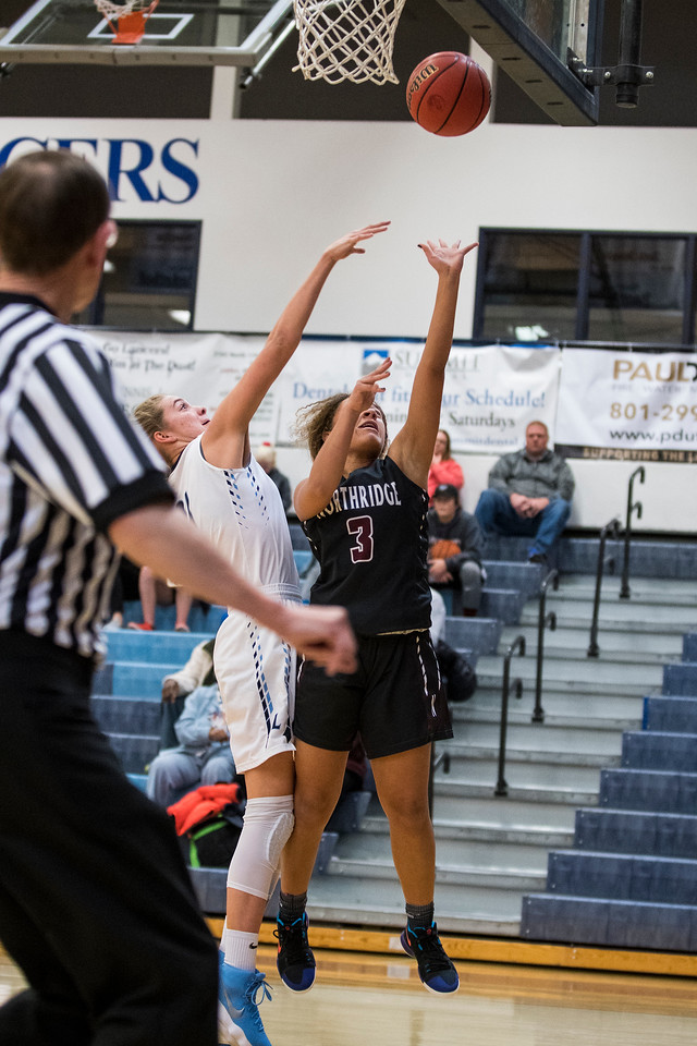 Brooklyn Perkins (3), of the Northridge Knights, capitalizes on a fast break opportunity and makes a lay-up despite the best efforts of Gracey Criswell (21), of the Layton Lancers, to make the stop, at Layton High School in Layton, on Wednesday, January 3, 2018. The Lancers held out against the Knights in a game full of lead changes to win 47-46, with the game coming down to the final seconds.