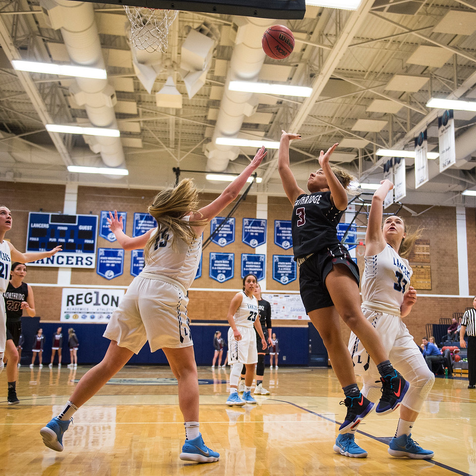 Brooklyn Perkins (3), of the Northridge Knights, drives from the perimeter past the defense of Layton players Kamryn Black (15) and Kaitlyn Viator (33), at Layton High School in Layton, on Wednesday, January 3, 2018.