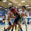 Blake Lamb (31), of Roy High, gets the offensive rebound and is immediately surrounded by Bonneville defenders Sealun Erskine (12) and Noah Atagi (42) at Bonneville High School on January 28, 2015. Lamb then forced his way through the defenders to make a lay up.