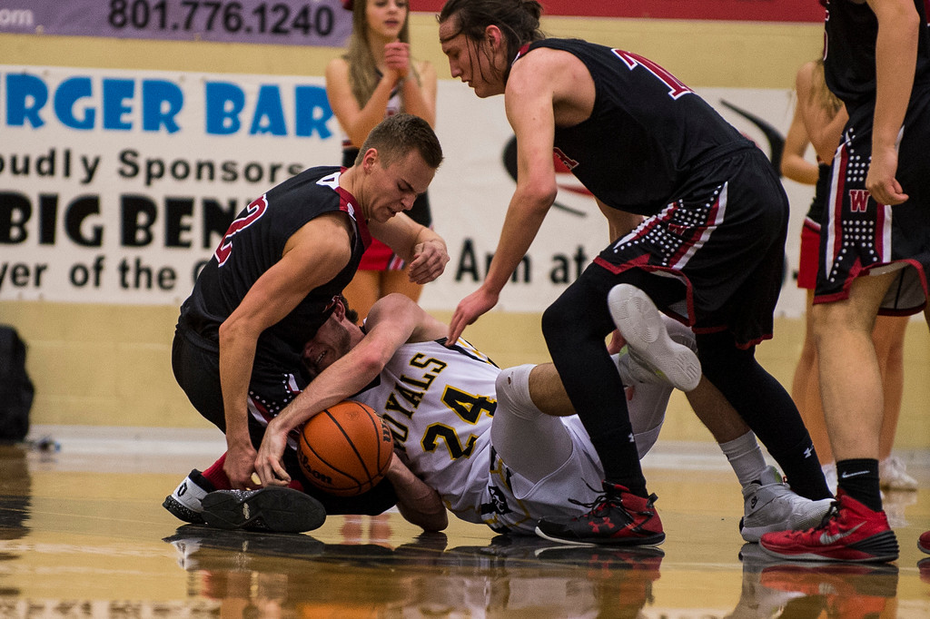 Roy High player, Justin Boley (24), fights to keep control of the ball on the ground against the defense of Austin Tolman (2), of Weber High, at Roy High School in Roy, on Friday, February 3, 2017.
