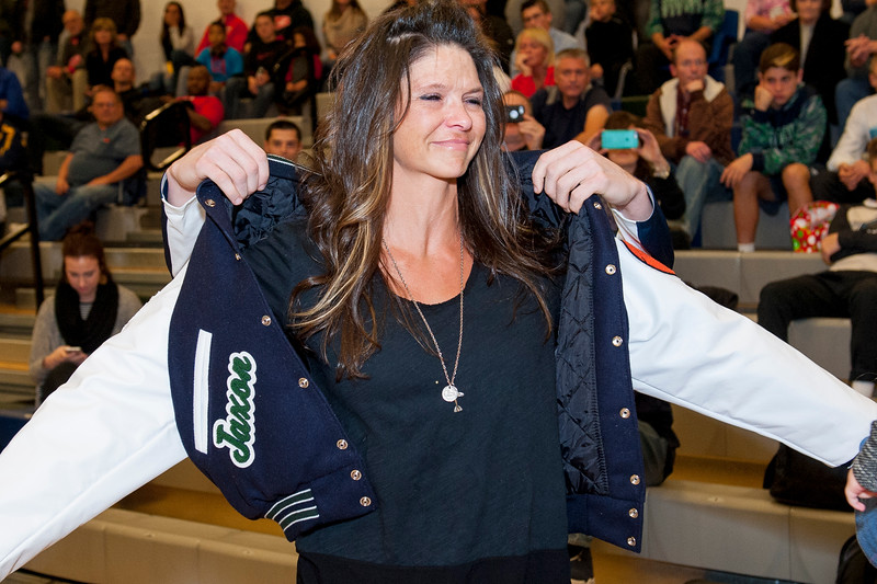 Eileen Whatcott puts on the letterman's jacket that was presented to her in honor of her sons, Jaxon and Daulton, that passed away in a plane crash in July of 2014; at Syracuse High School in Syracuse on December 16, 2015. Jaxon and Daulton were both former Syracuse High basketball players.