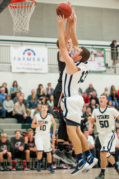 Andrew Carlson (13), of Syracuse drives to the basket and draws a foul from Weber High defender Austin Rushton (31) to go to the free throw line at Syracuse High School in Syracuse on December 16, 2015.