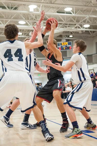 The Syracuse defense collapses around Spencer Campbell (15, black jersey) at Syracuse High School in Syracuse on December 16, 2015. Tough defense was the name of the game in the first half, with both teams making shot attempts labored.