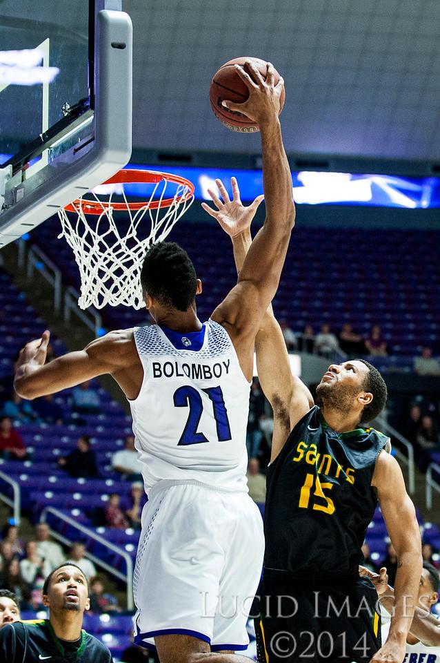 Joel Bolomboy (21), of Weber State, slam dunks the ball over Calvin Carr (15), of Presentation College, at the Dee Events Center in Ogden on November 17, 2014.