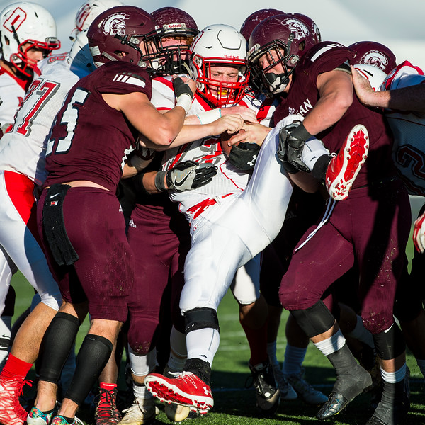 Jake Day (12), of the Delta Rabbits, gets wrapped up by four Morgan High players to stop a quarterback sneak in its tracks during a 3A semifinal playoff game at Stewart Stadium, in Ogden, on November 3, 2016.