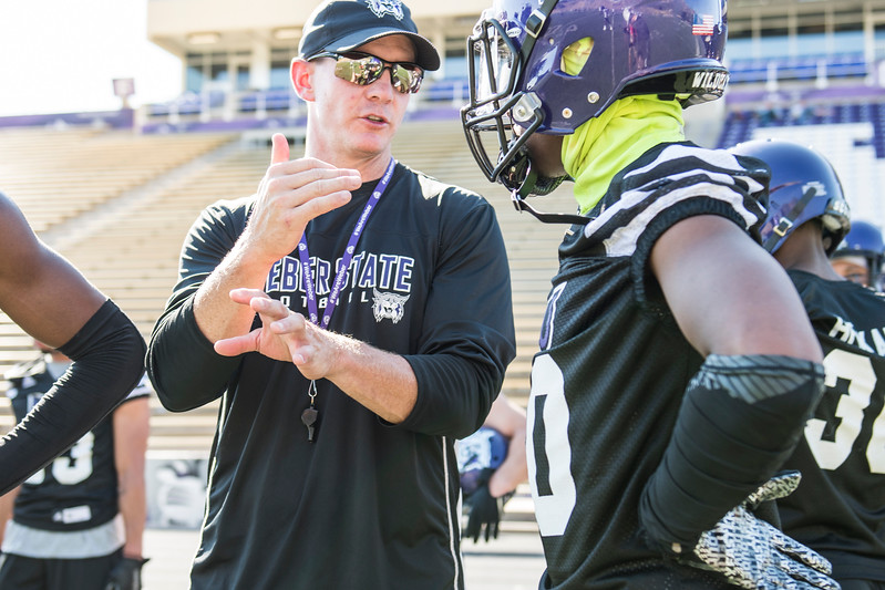 Weber State head coach, Jay Hill, talks with one his players, Keilan Benjamin (10), after Benjamin had blown coverage on a drill during the opening day of Weber's training camp, at Stewart Stadium, in Ogden, on Tuesday, August 1, 2017.