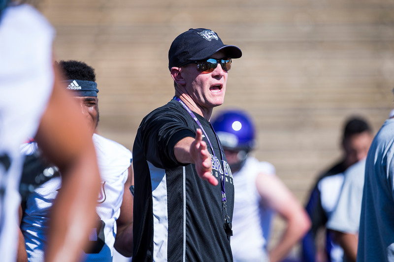 Weber State head coach, Jay Hill, motions for his players to give those running drills room near the line of scrimmage during the opening day of Weber's training camp, at Stewart Stadium, in Ogden, on Tuesday, August 1, 2017.