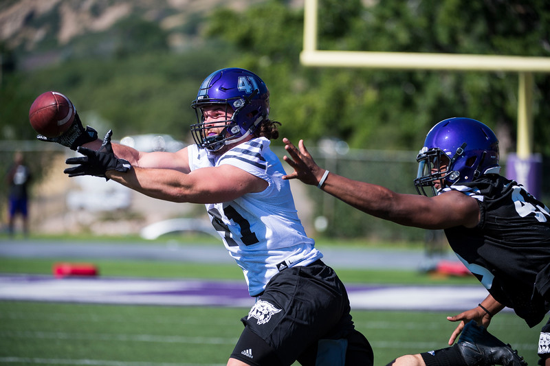 Weber State fullback, Brady May (41), extends for a catch against the defense of his teammate, Winston Reid (43), during the opening day of Weber's training camp, at Stewart Stadium, in Ogden, on Tuesday, August 1, 2017.