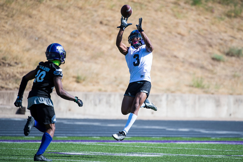 Wide receiver, Darryl Denby (3), goes airborne to catch the ball, leaving the defensive efforts of his teammate, Keilan Benjamin (10), far behind, during the opening day of Weber's training camp, at Stewart Stadium, in Ogden, on Tuesday, August 1, 2017.