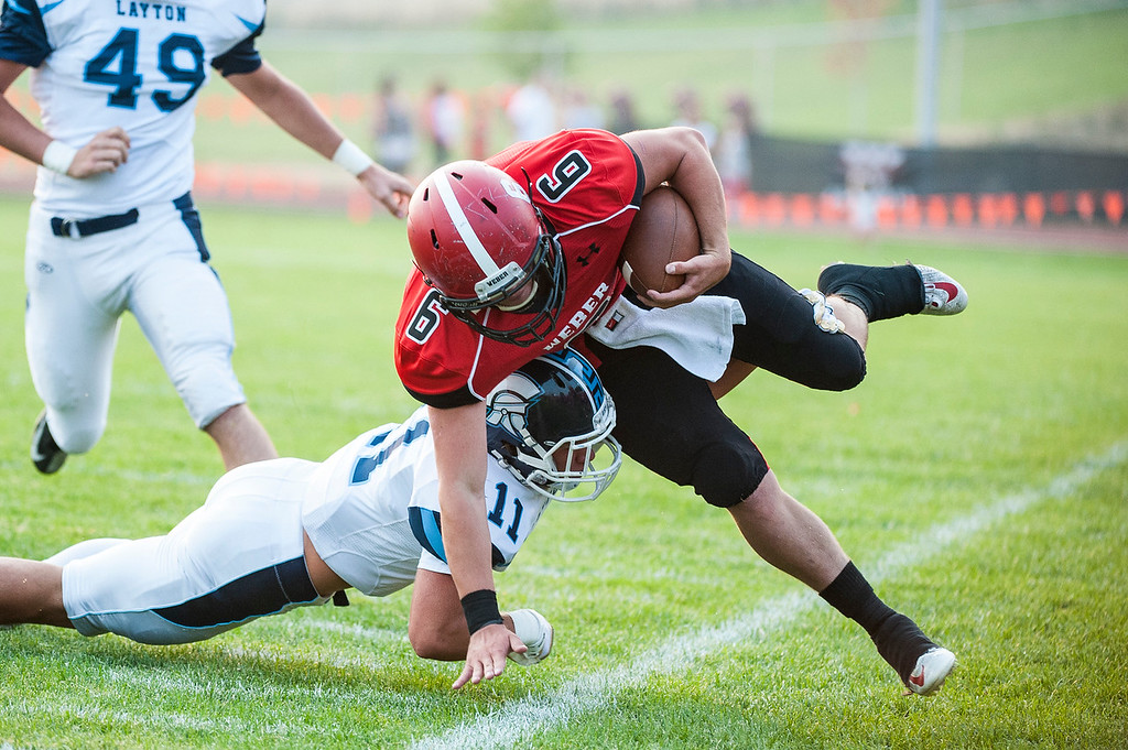 Garrett Hoyt (9), of Weber High, is pushed out of bounds by Layton defensive player Koy Cannon (11), after an eight yard pick up at Weber High School in Pleasant View on August 21, 2015.