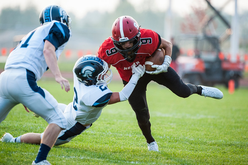 Weber High wide receiver, Brevin Dean (6), is brought down by Layton High defensive player, Garet Winkler (2), in the season opener at Weber High School in Pleasant View on August 21, 2015.