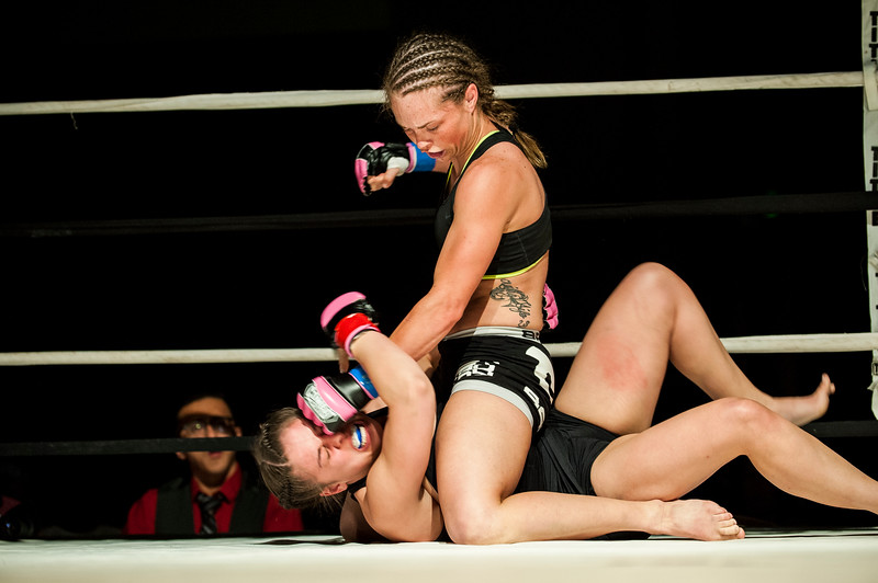 Brianna Wilding (top) lands some furious punches after mounting opponent Lisa Carroll (bottom) during the first of eight fights at Power Promotions' inaugural MMA card at the Davis Conference Center in Layton on April 4, 2015. Wilding would go on to win in the second round after a stoppage due to TKO.