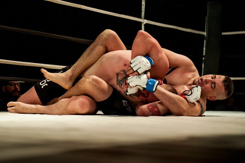 Jacob South (blue/white gloves) controls Jared Toothaker on the ground during the main event of Power Promotions inaugural MMA card April 4, 2015 at the Davis Conference Center on Layton.