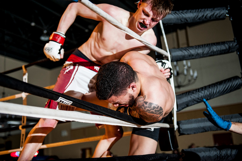 Cezly Collard (top) nearly forces his opponent Brandon Rease (lower) out of the ring during a closely fought bout at Power Promotions' inaugural MMA card at the Davis Conference Center in Layton on April 4, 2015. The fight would go to the scorecards and the judges declared Collard the winner by split decision.