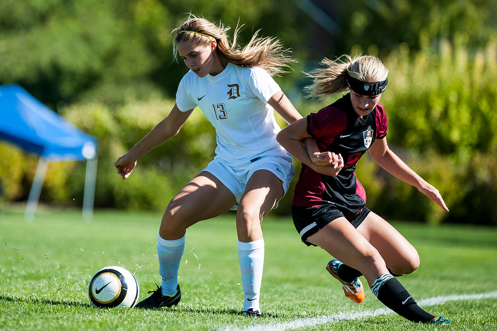 Davis forward Megan Rowe (13) works to keep the ball in bounds against Viewmont player Sam Draxler (9) while trying to get the ball turned towards Viewmont's goal in Kaysville on September 10, 2015.