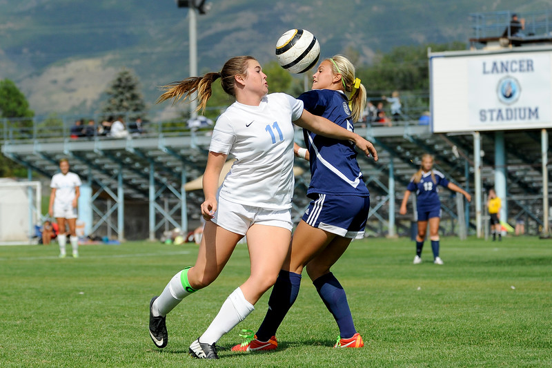 Kenzie Humpherys (left), of Layton High School, fights to gain control of the ball in the first half. Humpherys was an integral part of the Lancers' 4-2 victory, scoring three goals, against Syracuse High School in Layton on September 4, 2014. (ROBBY LLOYD/Standard-Examiner)