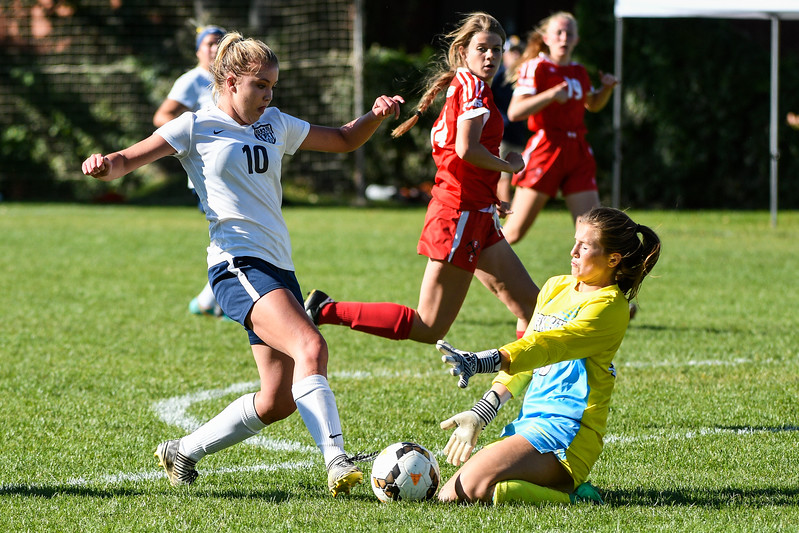 Park City's goalie, Emme Keizer (00), slides out to block and collide with Bonneville's Karly Conolly (10), drive on the goal at Bonneville High School, in Washington Terrace, on Wednesday, September 27, 2017. Keizer was kept busy all game by the relentless offense of Bonneville, allowing 8 goals to be scored.