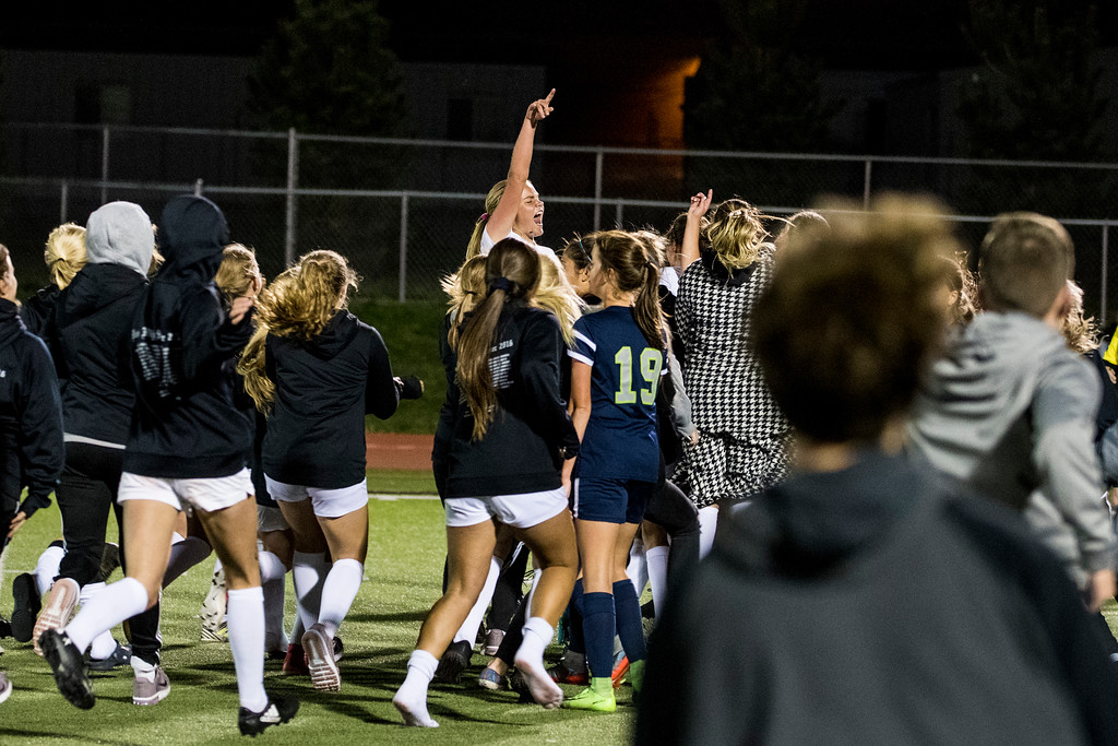 Olivia Romney (17, jumping) celebrates as the students of Davis High clear the stands after Alexa Maple (11), of Davis, scored the winning goal on a penalty kick in overtime after a hard fought game against Syracuse High, at Davis High School, in Kaysville, on Tuesday, September 26, 2017.