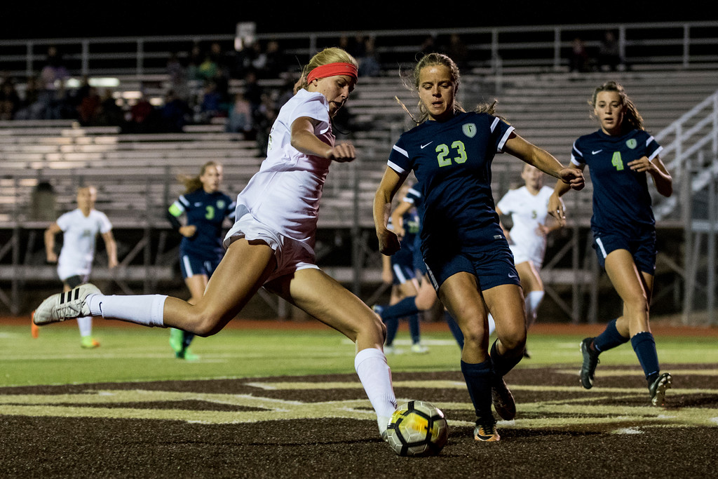 Olivia Griffin (21), of Davis, works to center the ball towards the goal against the defense of Abbie Riley (23), of Syracuse, at Davis High School, in Kaysville, on Tuesday, September 26, 2017.