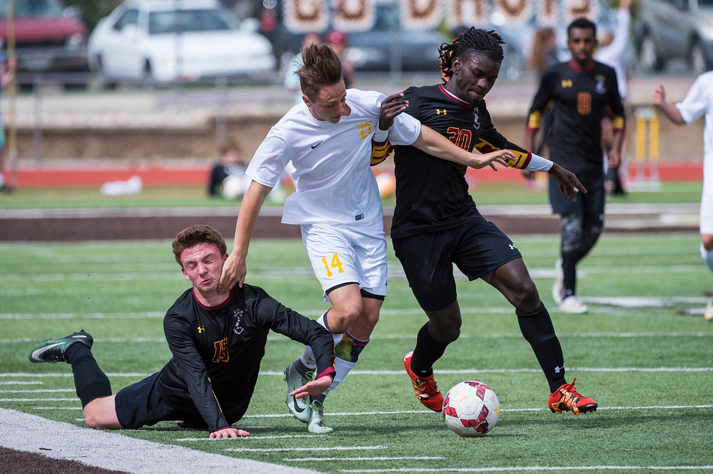 Cade Carter (14), of Davis High, tries to battle through the defense of Viewmont players James Ackley (15) and Elijah Moon (30) at Davis High School, in Kaysville, on Tuesday, April 25, 2017. Viewmont pulled out the win in the final 10 minutes, beating Davis 1-0.