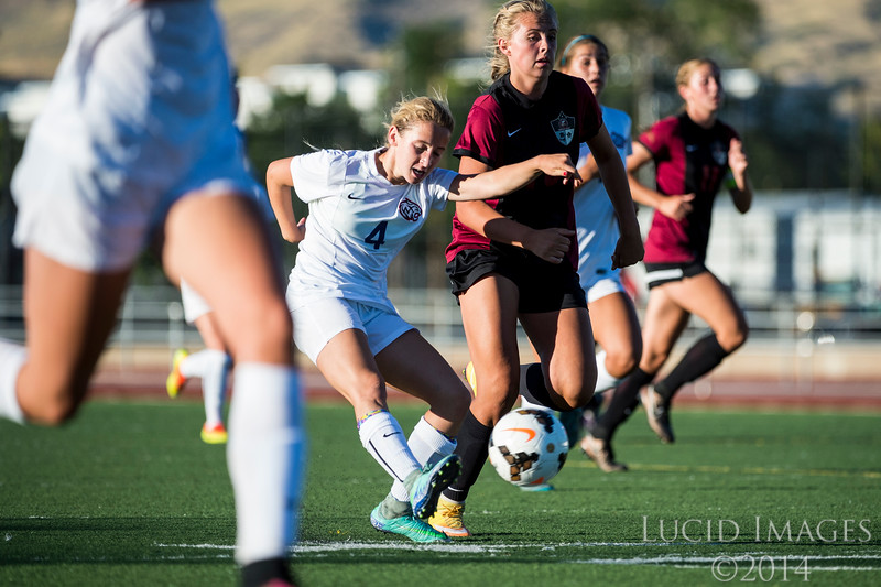 Woods Cross player, Camryn Henson (4), works to move the ball up the field past the defense of Viewmont defender, Sailor Uffens (10), at Woods Cross High School in Woods Cross on August 11, 2016.