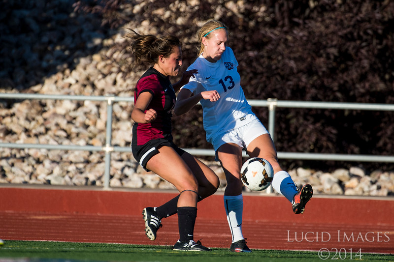 Sara Noel (13), of Woods Cross, crosses the ball in front of the Viewmont goal to try to create a scoring opportunity for her team despite the efforts of Viewmont defender, Isabelle Smith (26), to stop her at Woods Cross High School in Woods Cross on August 11, 2016.