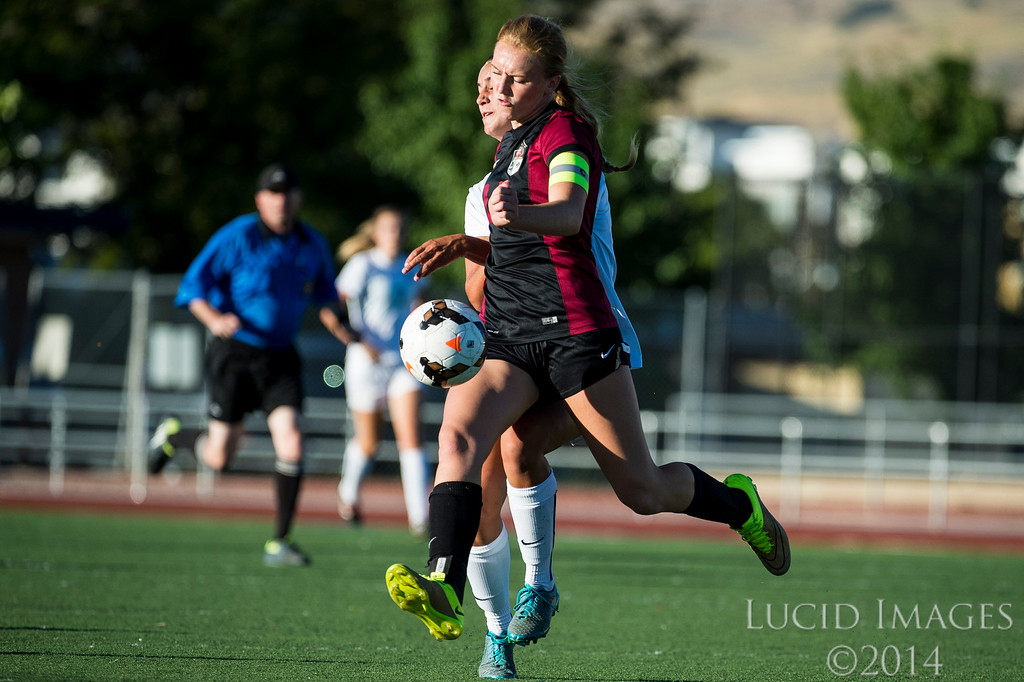 Grace Johnson (14), of Viewmont High, works to maintain control of the ball against the defense of Woods Cross player, Olivia Barton (11), at Woods Cross High School in Woods Cross on August 11, 2016.