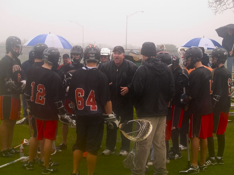 Coach Sowada preps the Westwood High School JV lacrosse team at half-time of their game with Anderson High School (in the pouring rain).