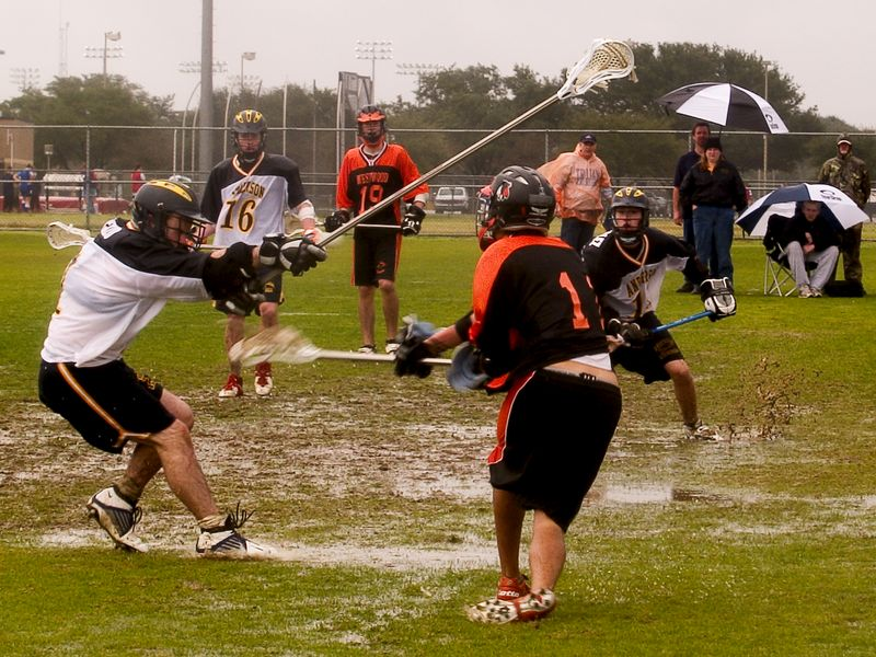 Pearson Suniga, attack,  uses a defender to block goalie as he shoots in the mud.